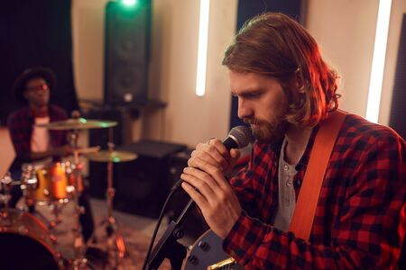 Side view portrait of handsome bearded man singing to microphone during rehearsal or concert with music band in dimly lit studio, copy space