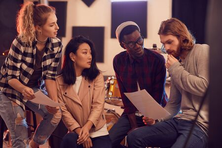 Multi-ethnic group of young people writing music together while rehearsing in record studio