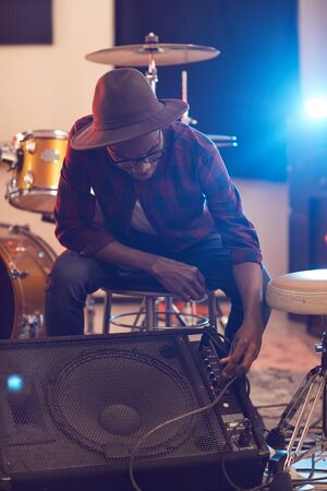 Full length portrait of contemporary African musician setting up guitar amplifier during sound check while preparing for concert or rehearsal with band in background