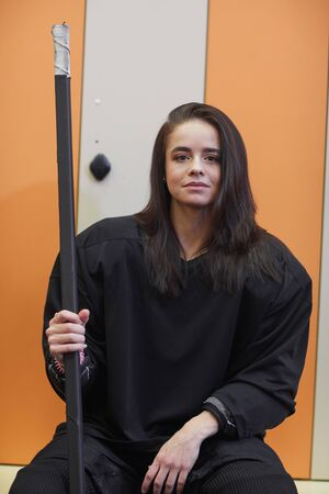 Portrait of beautiful young woman wearing hockey gear and looking at camera while posing in locker room Standard-Bild