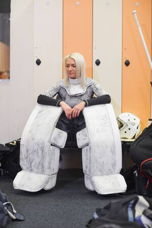 Full length portrait of sportive young woman wearing full hockey gear while sitting on bench in locker room, copy space