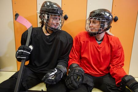 Portrait of two female hockey players smiling at each other in locker room while preparing for sports match or practice, copy space