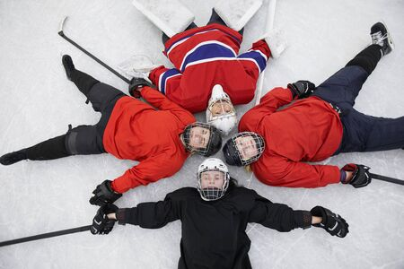 Top view of female hockey team lying on ice and looking at camera exhausted after practice, copy space