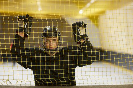 Waist up portrait of female hockey player looking at camera while standing behind gate net on rink, copy space