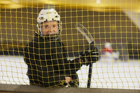 Waist up portrait of female hockey player smiling at camera while standing behind gate net on rink, copy space