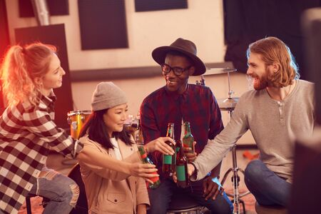 Multi-ethnic group of young people drinking beer while enjoying rehearsal in music studio Stock fotó