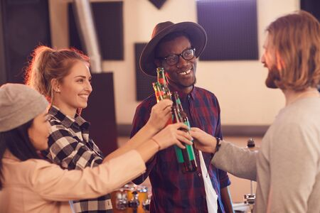 Multi-ethnic group of young people toasting with beer bottles while enjoying rehearsal in music studio