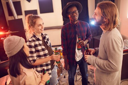 High angle view at multi-ethnic group of young people drinking beer and chatting while enjoying rehearsal in music studio Stock fotó