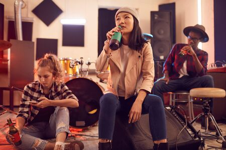 Multi-ethnic group of young people in music studio focus on Asian young woman drinking beet in foreground
