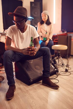 Full length portrait of trendy African man wearing hat and holding beer bottle while relaxing in music studio