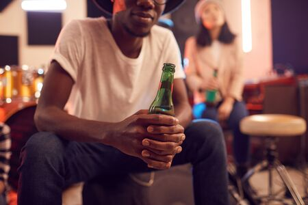 Mid-section portrait of trendy African man holding beer bottle while relaxing in music studio Stock fotó