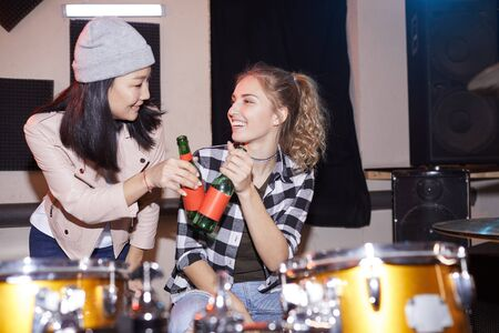 Portrait of two trendy young women clinking beer bottles in music studio, shot with flash