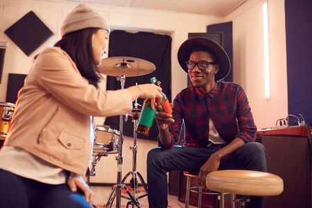Portrait of handsome African man clinking beer bottles with young woman while relaxing in music studio, copy space
