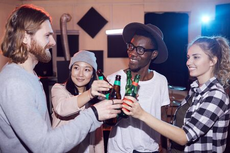 Multi-ethnic group of young people drinking beer and chatting while enjoying rehearsal in music studio, shot with flash