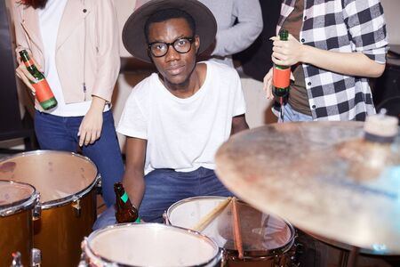 Portrait of African-American man posing by drum kit in music studio, shot with flash Stock Photo