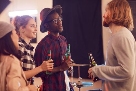 Multi-ethnic group of young people drinking beer and chatting while enjoying rehearsal in music studio Stock fotó