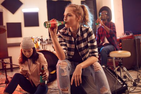 Multi-ethnic group of young people in music studio focus on pretty young woman drinking beet in foreground