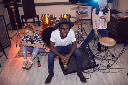 High angle portrait oif multi-ethnic group of young people sitting round instruments while relaxing in music studio, copy space