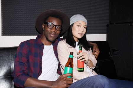 Portrait of modern young couple posing with beer bottles while enjoying nightclub party, shot with flash Stock fotó