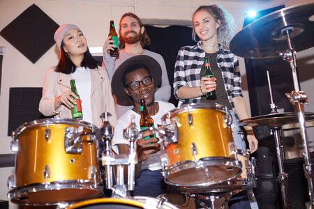 Portrait of multi-ethnic music band posing with beer bottles in studio, shot with flash