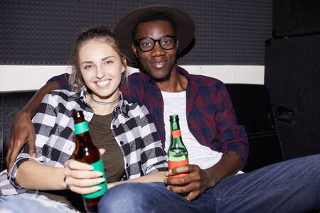 Portrait of modern young couple holding beer bottles while enjoying nightclub party, shot with flash Stock fotó