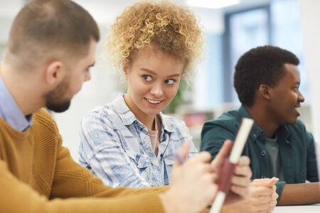 Multi-ethnic group of students sitting at desk in class, focus on cheerful young woman smiling at her friend