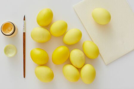 Above view of pastel yellow Easter eggs with paint brush arraigned in minimal composition on white background, copy space Stock Photo