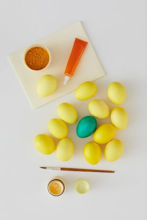 Above view of natural colored Easter eggs with green accent and paint brush arraigned in minimal composition on white background, copy space