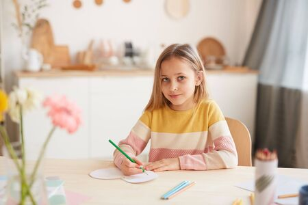 Warm toned portrait of cute little girl looking at camera and smiling while drawing pictures or doing homework while sitting at table in home interior, copy space