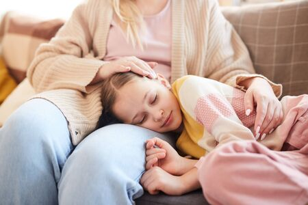 Retrato en tonos cálidos de linda chica durmiendo en el regazo de la madre mientras está acostada en el sofá en casa, espacio de copia