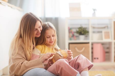 Warm-toned portrait of mother and daughter holding present while sitting on floor in cozy childrens room interior, copy space 版權商用圖片