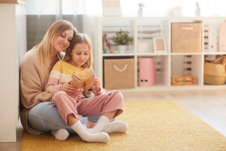 Full length portrait of mother and daughter holding present while sitting on floor in cozy childrens room interior, copy space