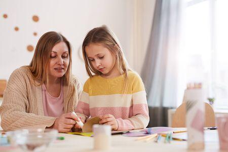 Portrait aux tons chauds d'une mère mature appréciant l'art et l'artisanat avec une jolie fille à l'intérieur de la maison, espace de copie