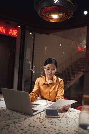Vertical portrait of Asian businesswoman using laptop while working late in dark office, copy space Stock Photo