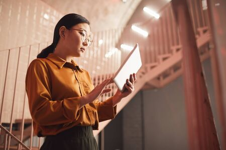 Side view portrait of young Asian businesswoman using tablet while standing by stairs outdoors, copy space