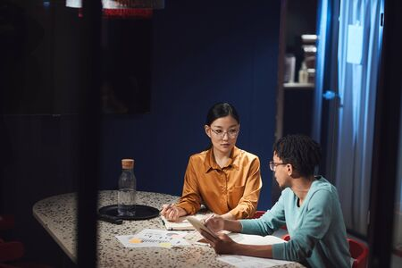 Portrait of Asian businesswoman talking to colleague while working late in dark office, cop space Stock Photo
