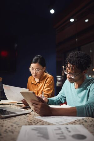 Vertical portrait of two ethnic business people discussing project while working late in dark office, copy space Stock Photo