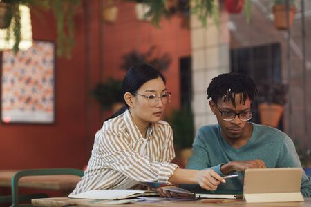 Portrait of two ethnic young people working on project together while sitting at table in cafe, copy space