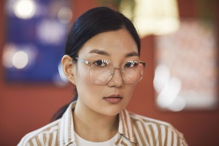 Head and shoulders portrait of young Asian woman wearing glasses looking at camera while posing against red wall in cafe, copy space Stock Photo