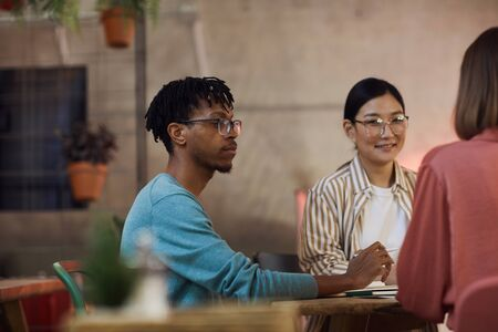 Multi-ethnic group of three young people working on project together while sitting at table in cafe, copy space Stock Photo