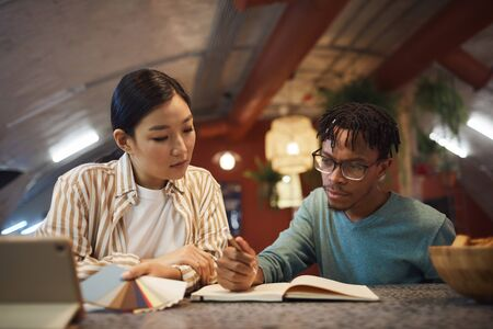 Portrait of two ethnic young people working on project together while sitting at table in office Stock Photo