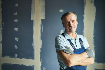 Waist up portrait of senior construction worker smiling at camera while posing confidently against dry wall, copy space