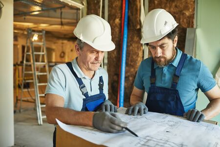 Waist up portrait of two construction workers wearing hardhats while looking at floor plans while renovating house, copy space
