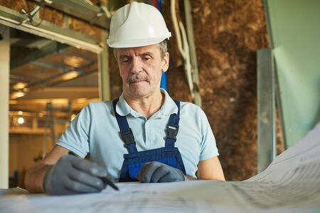 Waist up portrait of senior construction worker wearing hardhat while looking at floor plans while renovating house, copy space