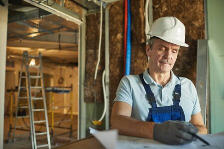 Waist up portrait of senior construction worker wearing hardhat and looking at floor plans while renovating house, copy space