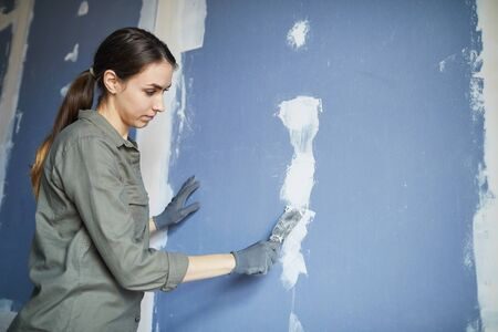 Waist up portrait of young woman smoothing dry wall while renovating house by herself, copy space Reklamní fotografie