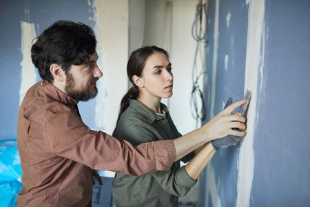 Waist up portrait of young couple smoothing dry wall while renovating house together, copy space Reklamní fotografie
