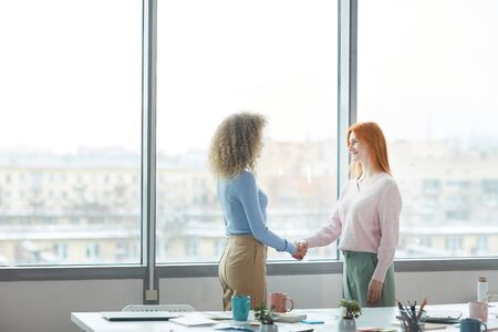 Side view portrait of two successful young businesswomen shaking hands after job interview or deal while standing by window in modern office, copy space