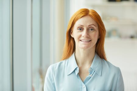 Head and shoulders portrait of red haired businesswoman smiling at camera while standing by window in modern white office, copy space Reklamní fotografie
