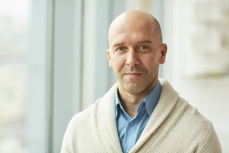 Head and shoulders portrait of balding mature man wearing cardigan looking at camera while standing by window in white office, copy space